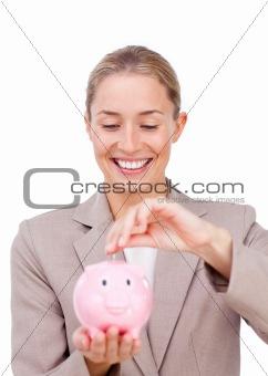 Charming businesswoman saving money in a piggybank