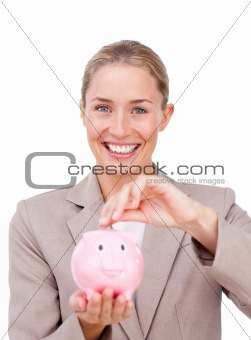 Assertive businesswoman saving money in a piggybank