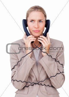 Angry businesswoman tangled up in phone wires