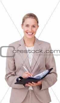 Assertive businesswoman making notes on her agenda