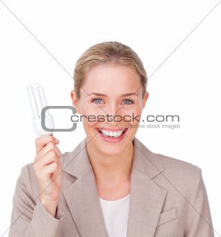 Positive businesswoman holding a saving energy light bulb