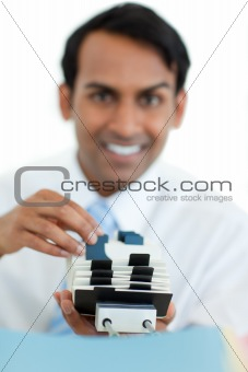 Smiling businessman consulting a business card holder