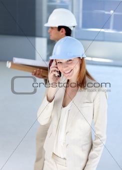 Smiling female architect on phone carrying blueprints