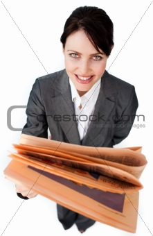 Assertive businesswoman reading a newspaper