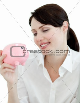 Attractive businesswoman looking at a piggybank