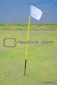 three golf balls on the putting green surrounding hole with a flag