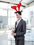 Smiling businesswoman with a novelty Christmas hat drinking Cham