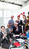 Business people with novelty Christmas hat toasting at a party