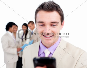 Charismatic businessman sending a text with a mobile phone with his team