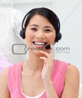 Positive Asian businesswoman talking on headset