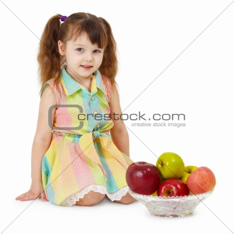 Little girl and dish filled with apples
