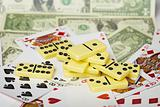 Several dominoes against cards and money