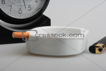 Clock and white ashtray with cigarette