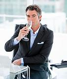 Confident businessman drinking a glass of water