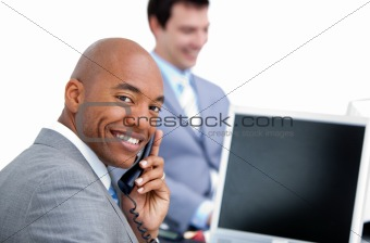 Happy businessman on phone and his colleague working at a comput