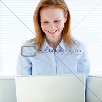Joyful business woman working on a laptop computer
