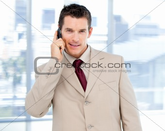 Assertive businessman talking on phone standing
