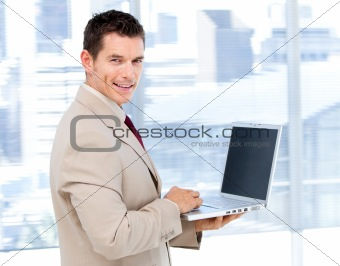 Positive businessman using a laptop standing