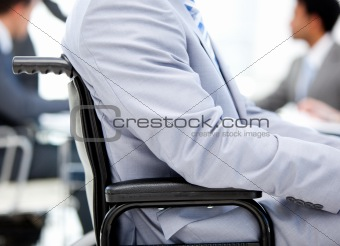 Close-up of a businessman sitting on a wheelchair