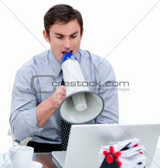 Angry businessman yelling through a megaphone sitting at his des