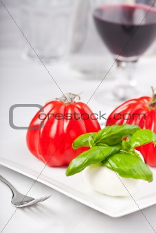 tomatoes, mozzarella and basil while making insalada caprese