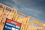 Sold Lot Real Estate Sign at New Home Framing Construction Site Against Deep Blue Sky.