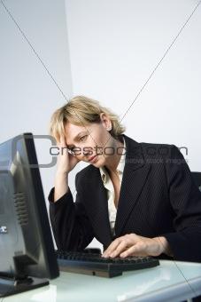 Businesswoman rubbing head.