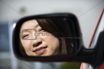 Smiling woman in car mirror