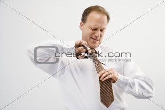 Businessman cutting necktie