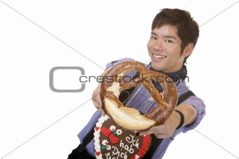 Asian man in Lederhose holds Oktoberfest pretzel in camera