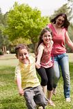 Family of three play in the park