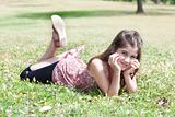 happy cute girl  laying on a grass field and looking stright