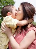 Children kissing his mom in the park