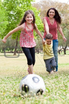 Childrens playing soccer with their mother