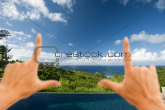 Hands Framing Breathtaking Hawaiian Ocean View Deck and Pool with Deep Blue Sky