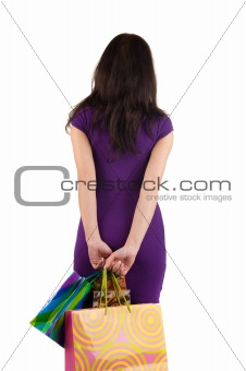 beautiful woman with shoping bags looking at wall.