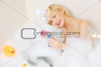 Smiling blond woman lying in bubble bath