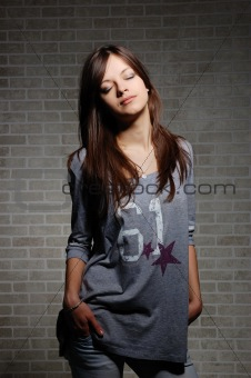 womanly brunette on brick wall background .