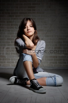 Sitting brunette girl in gym shoes.
