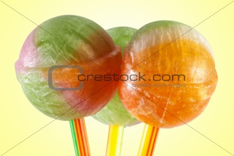 three multicolor lollipop candy