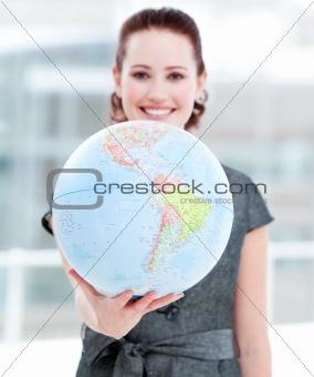 Assertive businesswoman holding a terrestrial globe
