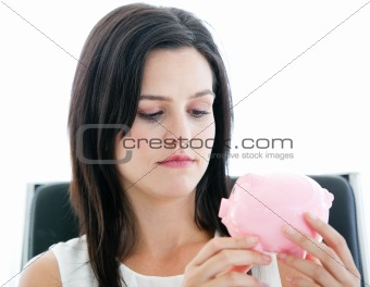 Beautiful businesswoman holding a piggybank