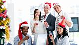 Smiling business team drinking champagne to celebrate christmas