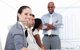 Smiling businesswoman looking at the camera during a meeting wit