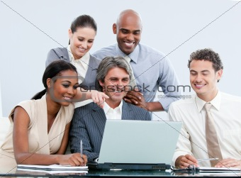 Joyful internationnal businessteam looking at the laptop
