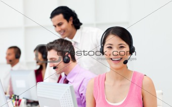 Portrait of an Asian customer agent and her team