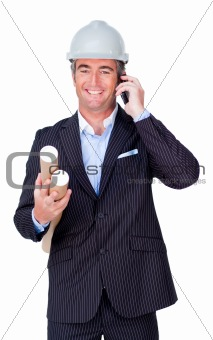 Smiling businessman on phone and holding blueprints