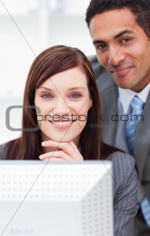 Two smiling colleagues working at a computer