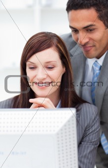 Two enthusiastic colleagues working at a computer