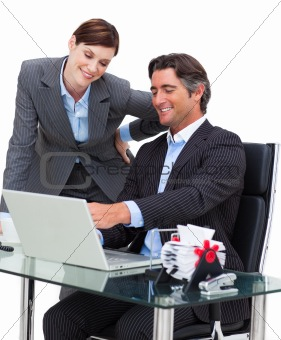 Assertive businessman showing something on computer to his colle